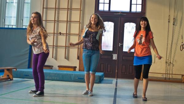 Bei den Proben in der Turnhalle von Emmas Hamburger Schule versucht Ally tapfer zu sein. v.li.: Ally (Marny Kennedy), Emma (Sophie Karbjinski), Jackie (Charlotte Nicdao) | Rechte: NDR/Southern Star