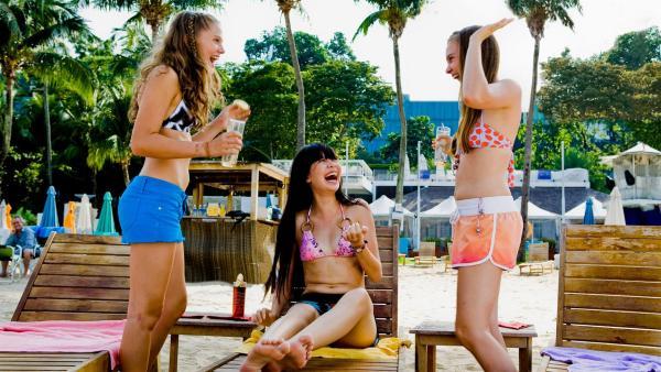 Emma (Sophie Karbjinski, li.), Jackie (Charlotte Nicdao, Mi.) und Ally (Marny Kennedy, re.) haben Spaß am Strand von Singapur. | Rechte: NDR/Southern Star