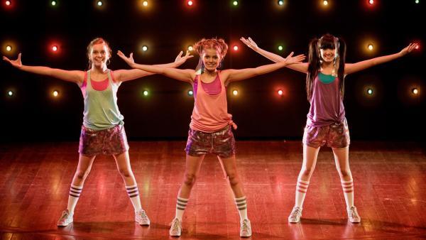 Emma (Sophie Karbjinski, Mitte), Ally (Marny Kennedy, li.) und Jackie (Charlotte Nicdao, re.) strahlen: Sie dürfen am begehrten Tanzworkshop teilnehmen. | Rechte: NDR/Southern Star