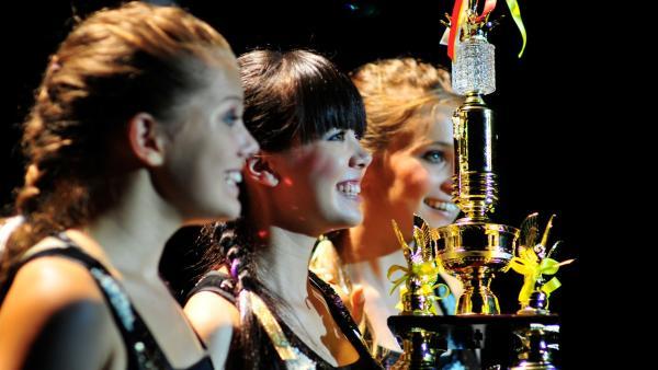 Die Mädchen träumen davon, die Trophäe zu gewinnen. V.l.:Emma (Sophie Karbjinski), Jackie (Charlotte Nicdao) und Ally (Marny Kennedy). | Rechte: NDR/Southern Star