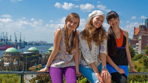 Ally, Emma und Jackie sitzen auf einem Geländer am Hafen von Hamburg | Rechte: NDR/Southern Star