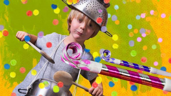 Ein Junge mit Nudelsieb auf dem Kopf trommelt mit zwei Holzkochlöffeln auf einen Topf. Er macht laute Geräusche.  | Rechte: KiKA