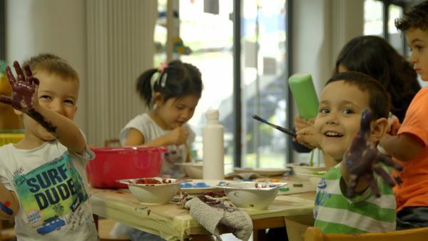 Yeganeh und ihre Freunde bemalen Kronkorken. | Rechte: KiKA