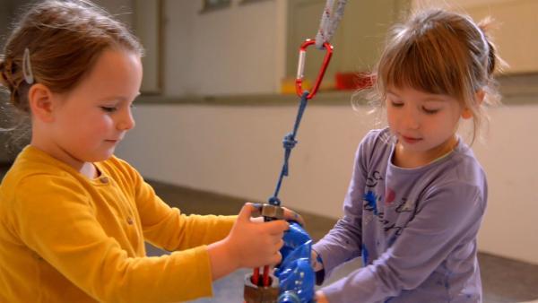 Emelie und Frieda füllen Farbe in das Pendel. | Rechte: KiKA