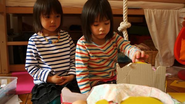 Yuna und Mina verzieren ihre Puppenwiege. | Rechte: KiKA