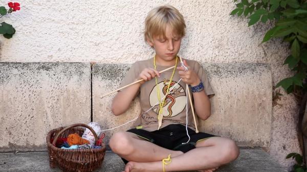 Korbinian fängt an zu stricken. | Rechte: KiKA