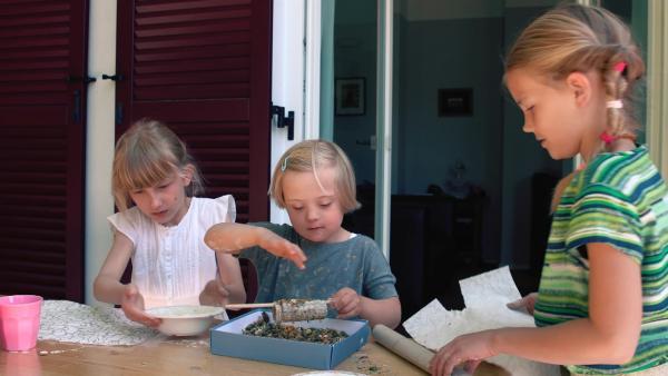 Sophie, Helena und Antonia bestreuen Toilettenpapierrollen mit Futter. | Rechte: KiKA