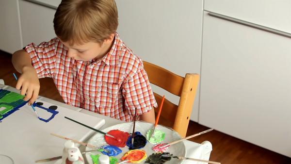Manuel malt mit Pinsel und Farbe. | Rechte: KiKA