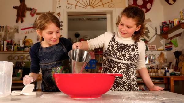 Lisbeth und Lara mischen Maisstärke und Wasser | Rechte: KiKA