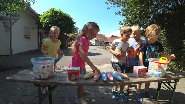 Quinn, Jolie, Larissa, Hanno, Leo und Bennet holen sich Kreide zum Malen. | Rechte: KiKA
