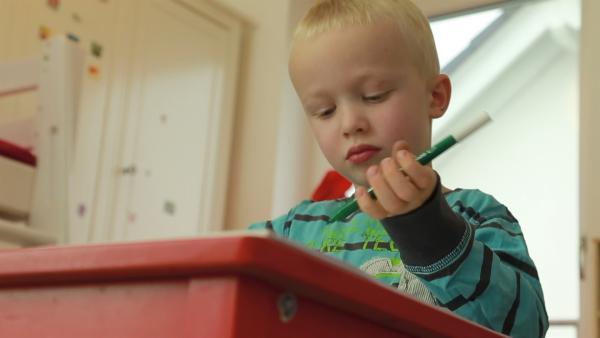 Johann malt mit einem Filzstift. | Rechte: KiKA