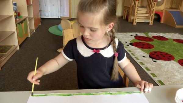 Lena malt mit Pinsel und Tusche. | Rechte: KiKA