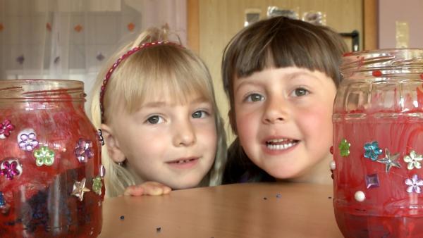 Anna und Sophie zeigen ihre Windlichter. | Rechte: KiKA