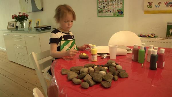 Leni malt einen Stein an. | Rechte: KiKA