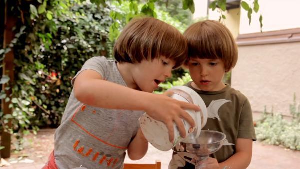 Theo und Otto füllen Gips in einen Trichter. | Rechte: KiKA