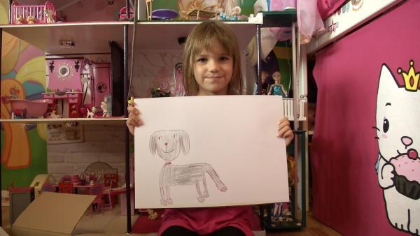 Mia zeigt ihr gemaltes Bild. | Rechte: KiKA