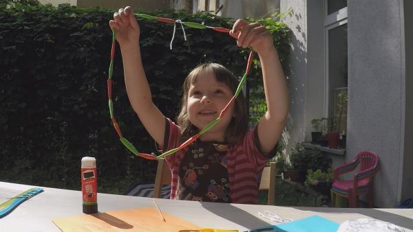 Anna zeigt ihre Papierkette. | Rechte: KiKA