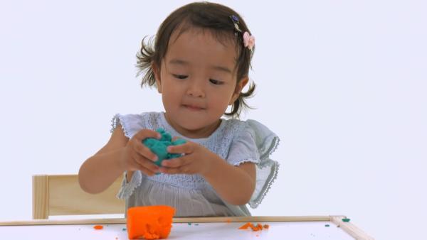 Ida spielt mit bunter Knete.   Rechte: KiKA/Motion Works GmbH