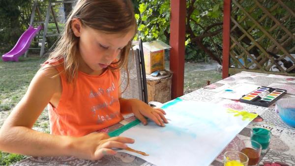 Leonie malt mit brauner Farbe. | Rechte: KiKA