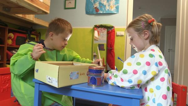 Jacob und Sofia malen einen Schuhkarton an. | Rechte: KiKA
