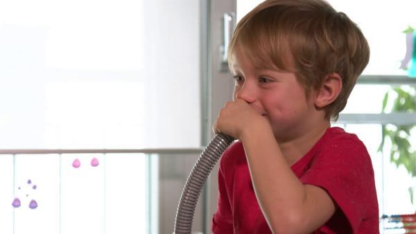 Ein Junge bläßt in einen Plastikschlauch. | Rechte: KiKA