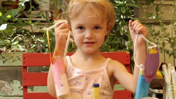 Isabel zeigt ihre gebastelten Figuren. | Rechte: KiKA