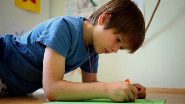 Julian malt ein Bild. | Rechte: KiKA