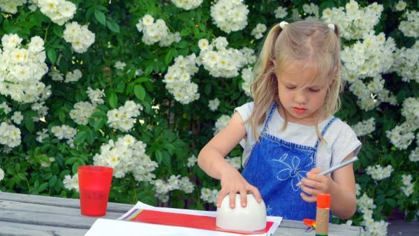 Luisa malt Kreise auf buntes Papier. | Rechte: KiKA
