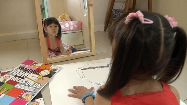 Karnpicha schaut sich im Spiegel an. | Rechte: KiKA