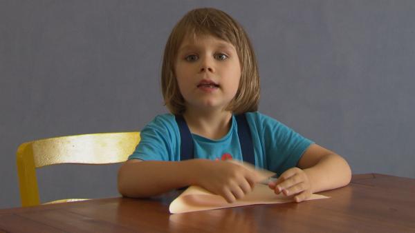 Robert faltet ein Blatt Papier. | Rechte: KiKA