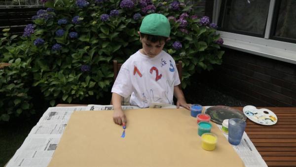 Gökay malt mit Fingermalfarben. | Rechte: KiKA