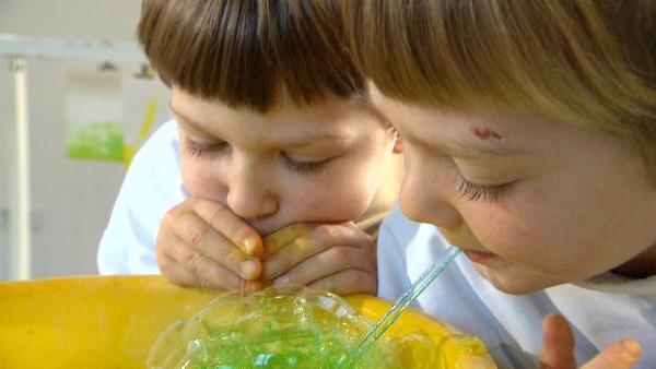 Linus und Lasse machen bunte Seifenblasen. | Rechte: KiKA