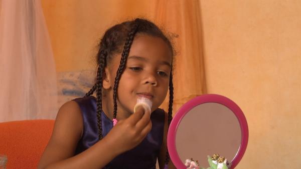 Victorine schminkt sich ein Clowngesicht. | Rechte: KiKA