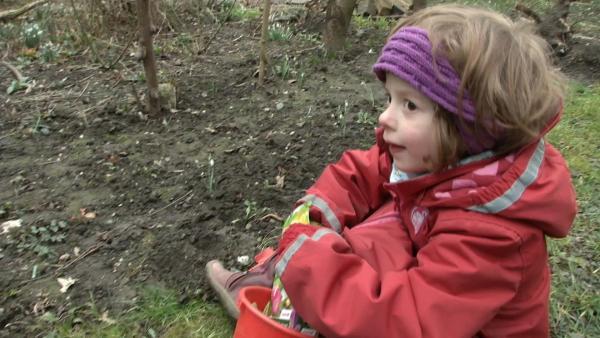 Matilda nimmt eine Blumenzwiebel aus ihrem Eimer. | Rechte: KiKA