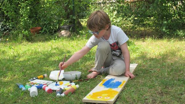 Liam malt auf Holz. | Rechte: KiKA/Motion Works GmbH