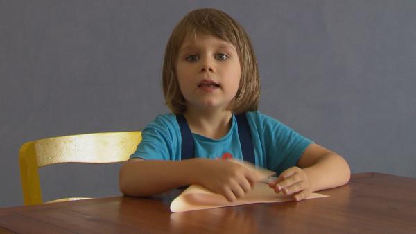 Robert faltet ein Blatt Papier. | Rechte: KiKA/Motion Works GmbH