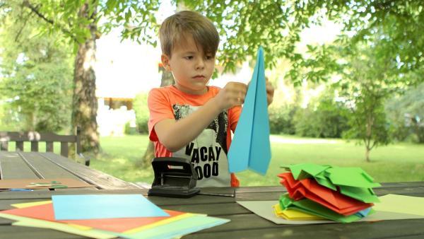 Adnan faltet einen blauen Papierflieger. | Rechte: KiKA/Motion Works GmbH