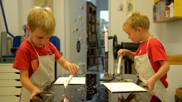 Justus und Lorenz verteilen Wachstropfen auf ihren Blättern. | Rechte: KiKA/Motion Works GmbH