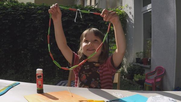 Anna bastelt eine Kette aus Papier. | Rechte: KiKA/Motion Works GmbH