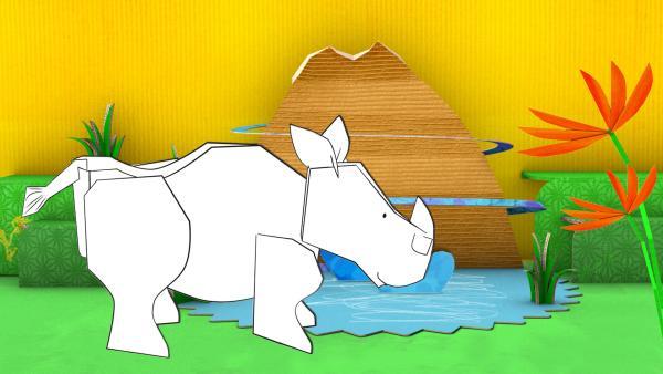 Das gebastelte Nashorn aus Papier von ENE MENE BU trinkt aus einem See vor einem Berg.   Rechte: KiKA