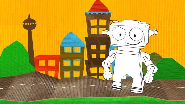 Der gebastelte Roboter aus Papier von ENE MENE BU in einer Stadtlandschaft.   Rechte: KiKA