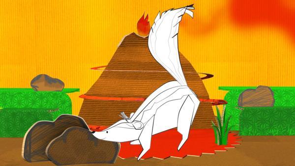 Das gebastelte Stinktier aus Papier von ENE MENE BU in einer Vulkanlandschaft.   Rechte: KiKA