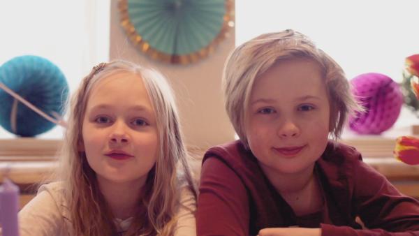 Anna und Jona sitzen in ihrer geschmückten Küche und schauen direkt in die Kamera. | Rechte: KiKA