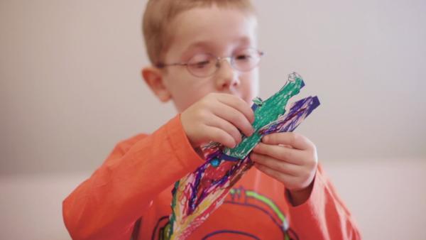 Ein Junge bastelt ein Steckkrokodil aus Papier. Das Krokodil ist mit Filzstiften in lila und grün angemalt. | Rechte: KiKA