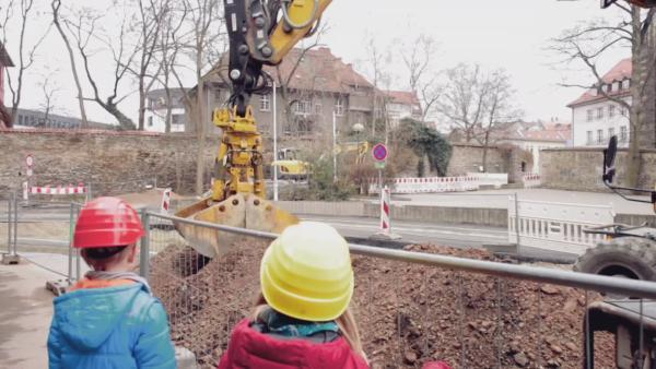 Zwei Kinder beobachten einen Bagger auf der Baustelle. | Rechte: KiKA