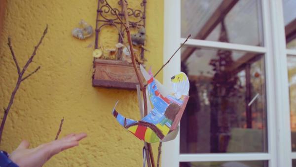 Ein bunt bemaltes Steckfaultier von ENE MENE BU an einem Ast. | Rechte: KiKA