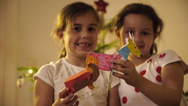 Emma und Ida halten ihren selbstgebastelten, bunt bemalten Steckhirsch mit einem Schlitten aus Pappe hoch. | Rechte: KiKA