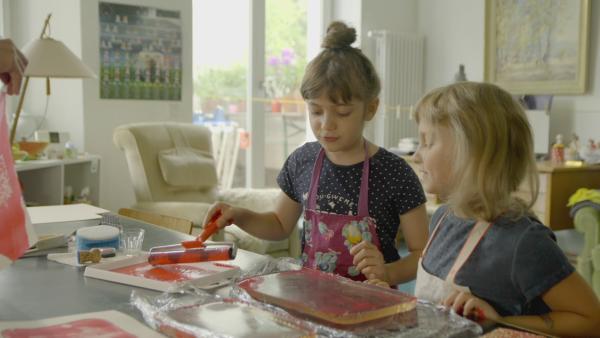 Zwei Mädchen rollen mit einer Farbwalze rote Farbe auf eine Gelatineplatte.  | Rechte: KiKA