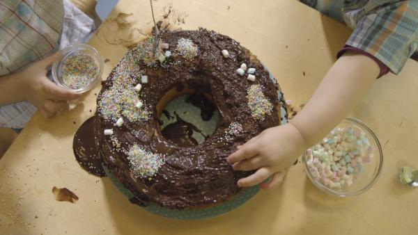 Kinder dekorieren einen Kuchen mit bunten Streuseln, Marshmallows und Gummibärchen | Rechte: KiKA