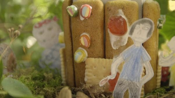 Hänsel, der aus Papier selber gemalt wurde, steht vor einem Keks-Hexenhaus aus dem die Hexe herausschaut. | Rechte: KiKA